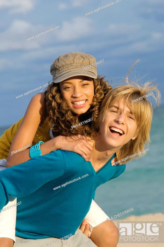 Stock Photo: Girl riding piggyback on a teenage boy on the beach.