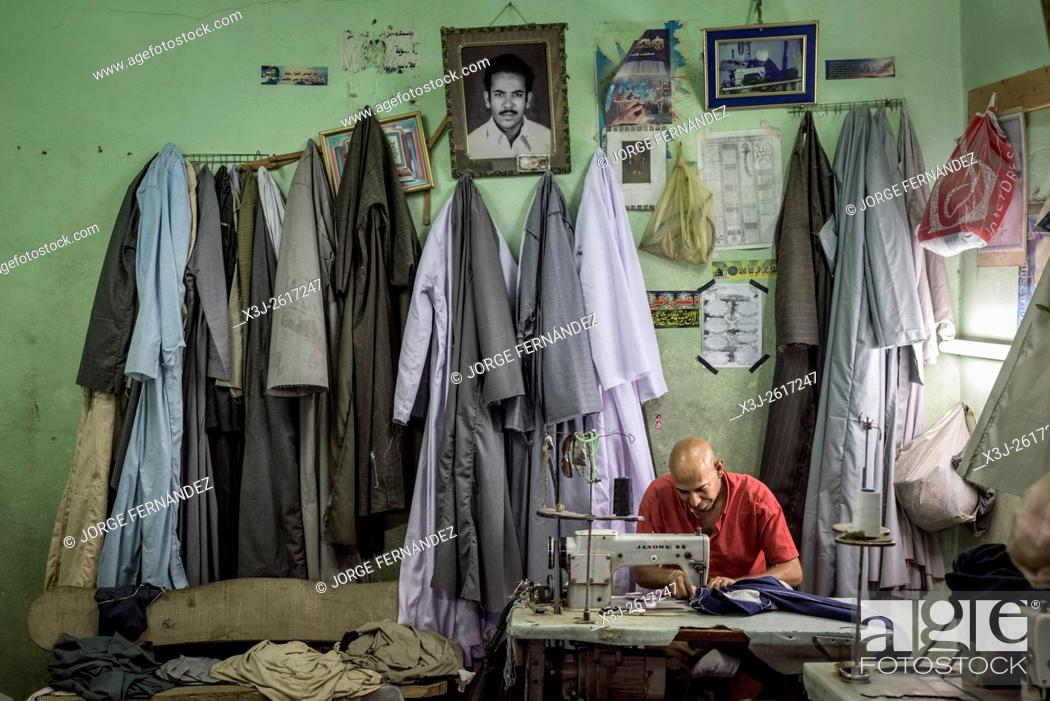 Imagen: Tailor sewing clothes inside his workshop.