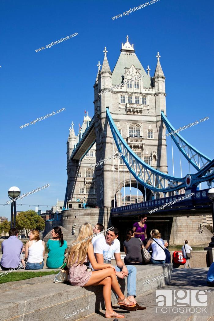 Stock Photo: Tourists sitting near a bridge, Tower Bridge, Thames River, London, England.