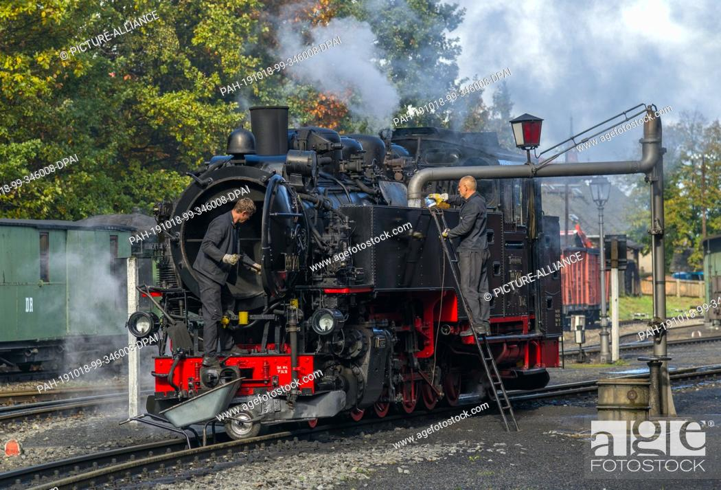 Stock Photo: 10 October 2019, Saxony, Bertsdorf: At the station, water is filled into a locomotive of the Zittau narrow-gauge railway.