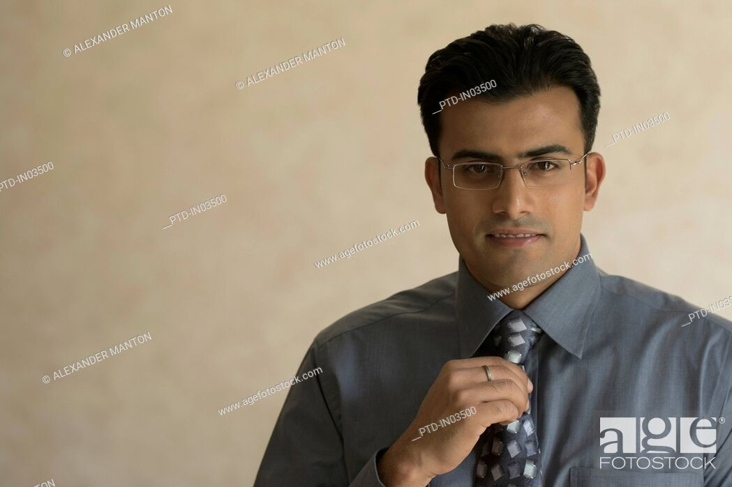 Stock Photo: India, Portrait of young businessman adjusting his tie.