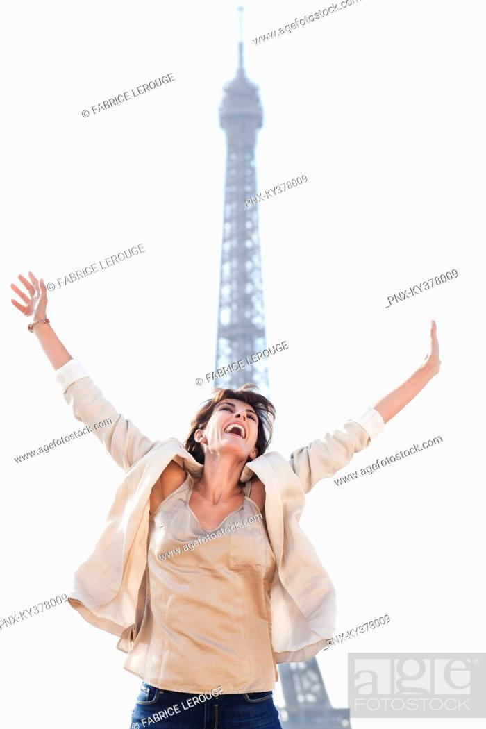 Stock Photo: Woman shouting in excitement with the Eiffel Tower in the background, Paris, Ile-de-France, France.