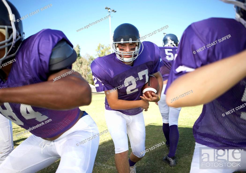 Stock Photo: Football player running behind linemen on field.