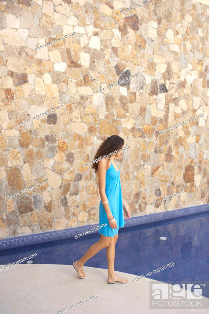 Stock Photo: Woman walking next to hotel pool, Los Cabos, Mexico.