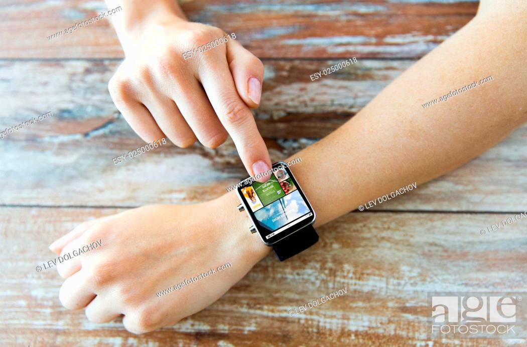 Stock Photo: business, modern technology, media, internet and people concept - close up of female hands setting smart watch with news web page on screen on wooden table.