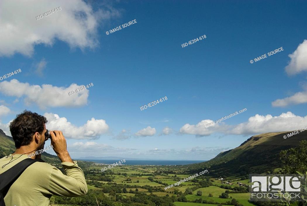 Stock Photo: Man looking at glenariff with binoculars.