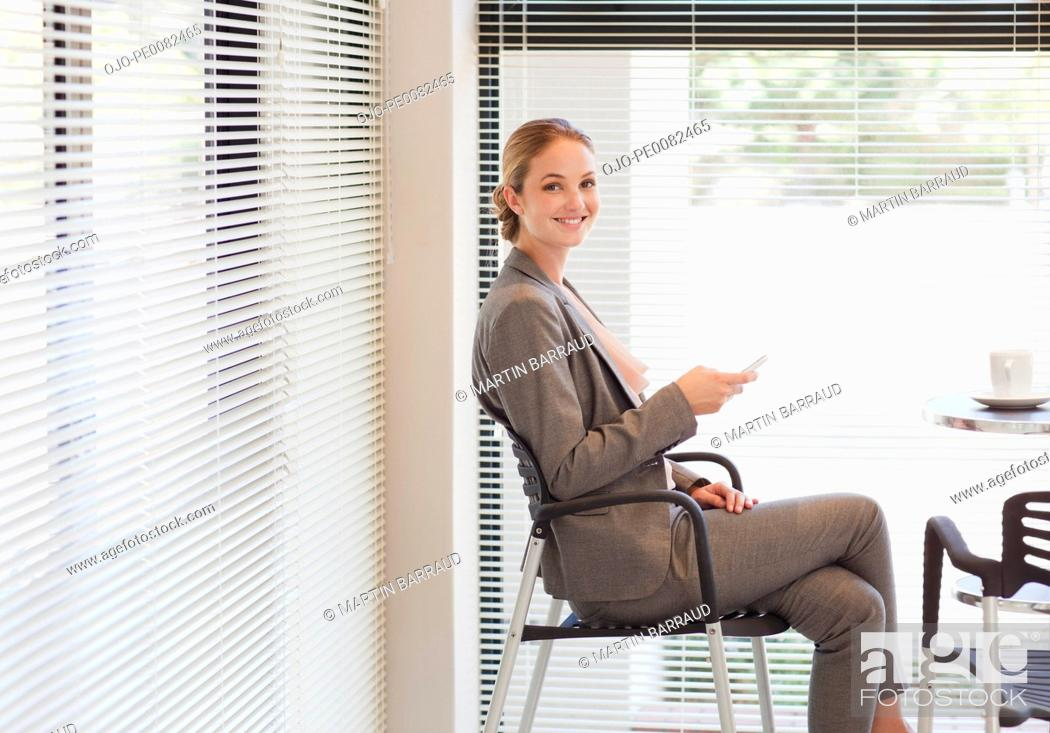 Stock Photo: Portrait of smiling businesswoman holding cell phone in cafeteria.