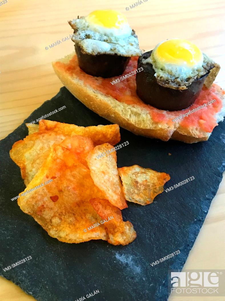 Stock Photo: Spanish tapa made of morcilla and quail eggs on bread with tomato and chips. Spain.