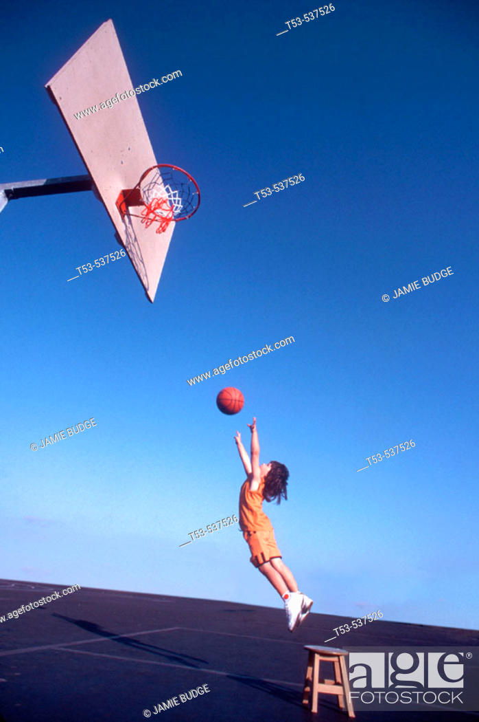 Stock Photo: 4 1/2 year old child budge shoots a hoop with the help of his stool.