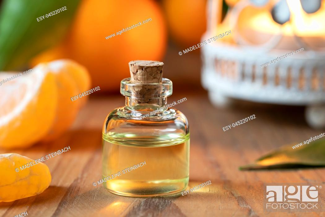 Stock Photo: A bottle of citrus essential oil with fresh tangerines.