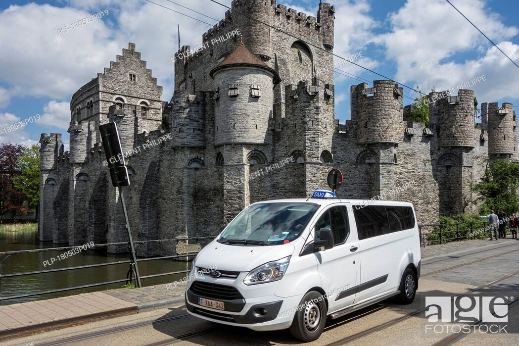 Stock Photo: Taxi riding in front of the Gravensteen / Castle of the Counts in the historic city centre of Ghent, East Flanders, Belgium.