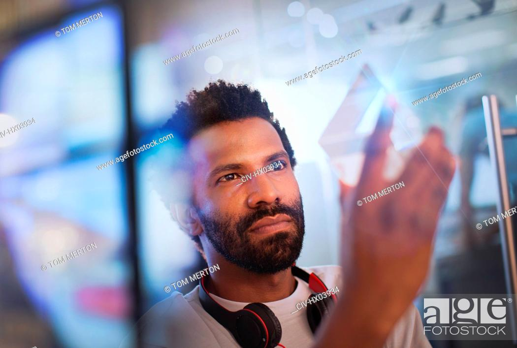 Stock Photo: Focused, innovative male entrepreneur examining glass triangle prototype.