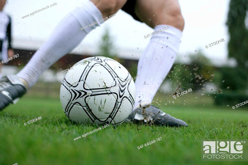 Stock Photo: Soccer player kicking a football.