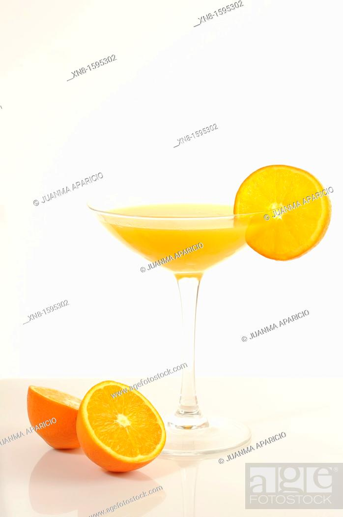 Stock Photo: Orange juice cocktail glass garnished with orange slice on the rim of the cup on white background and an orange cut in half at the bottom of the cup.