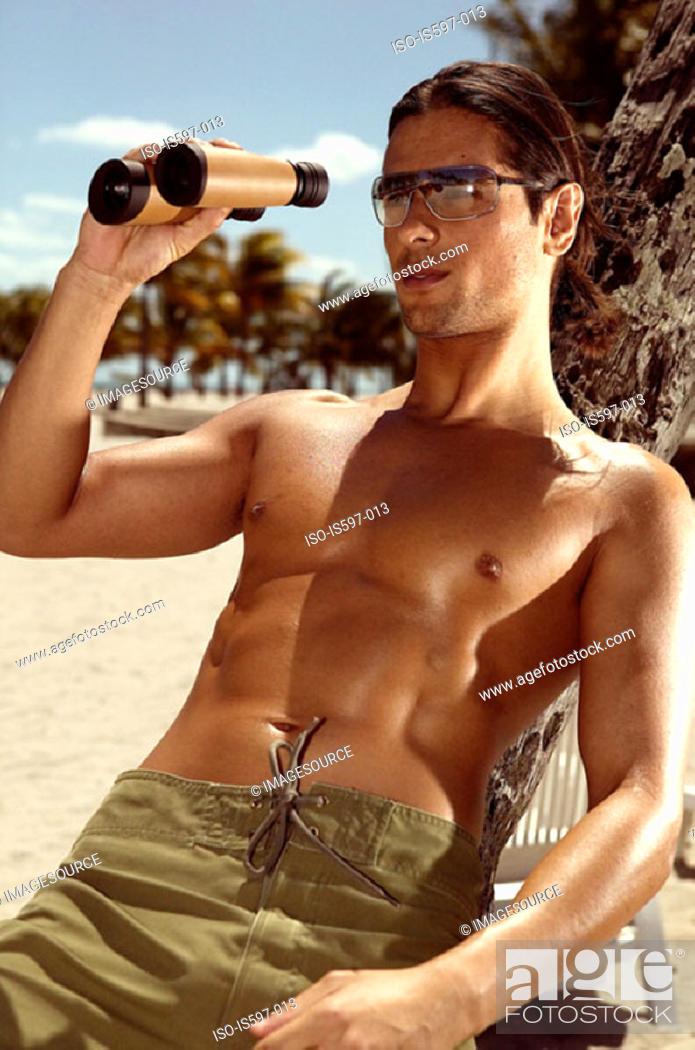 Stock Photo: Man using binoculars on beach.