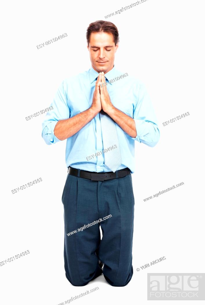 Stock Photo: Portrait of mature male executive on his knees praying isolated on white background.