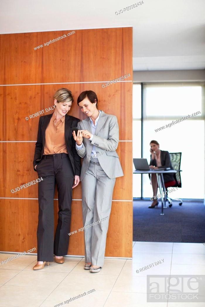 Stock Photo: Businesswomen looking at cell phone in office corridor.