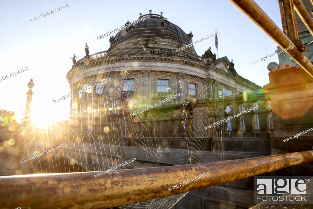Imagen: 13 July 2020, Berlin: In front of the Bode-Museum, a spider's web hangs from a railing, with the sun going out. After two years of evaluation of the Prussian.
