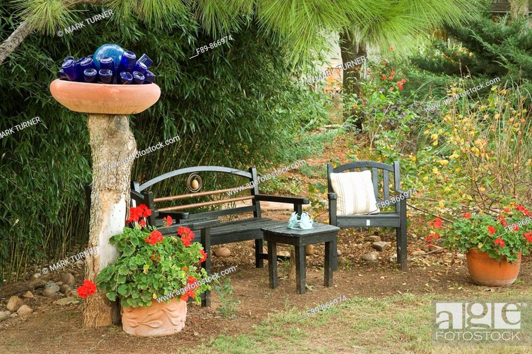 Stock Photo: Blue bottles in bowl on post above bench & chairs framed by Geraniums in containers with bamboo hedge.