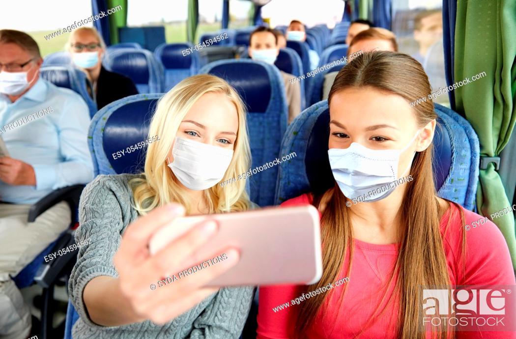 Stock Photo: women in medical masks taking selfie in travel bus.