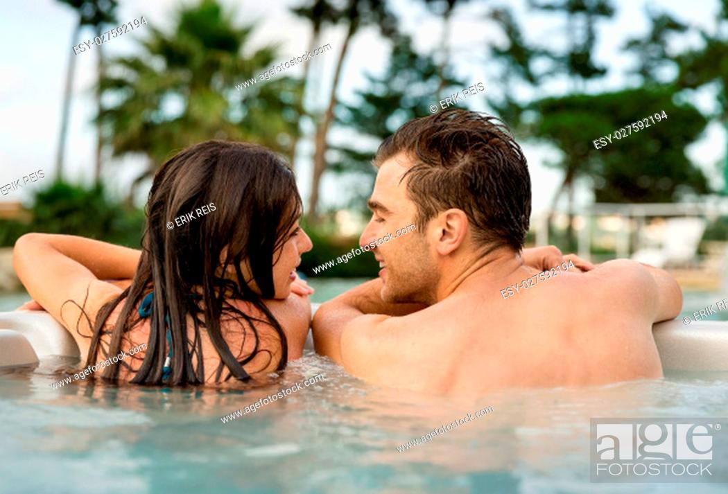 Stock Photo: Young couple in a luxury hotel inside a jacuzzi in a rainy day.