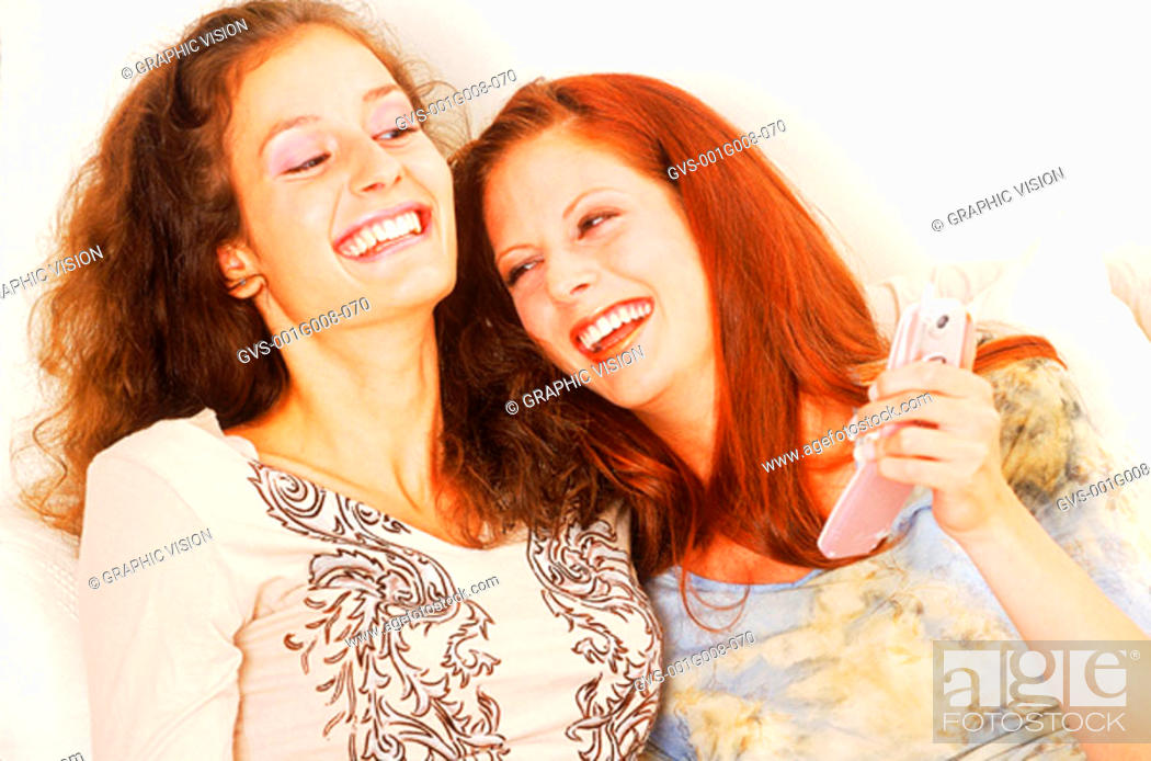 Stock Photo: Two young women laughing and holding a mobile phone.