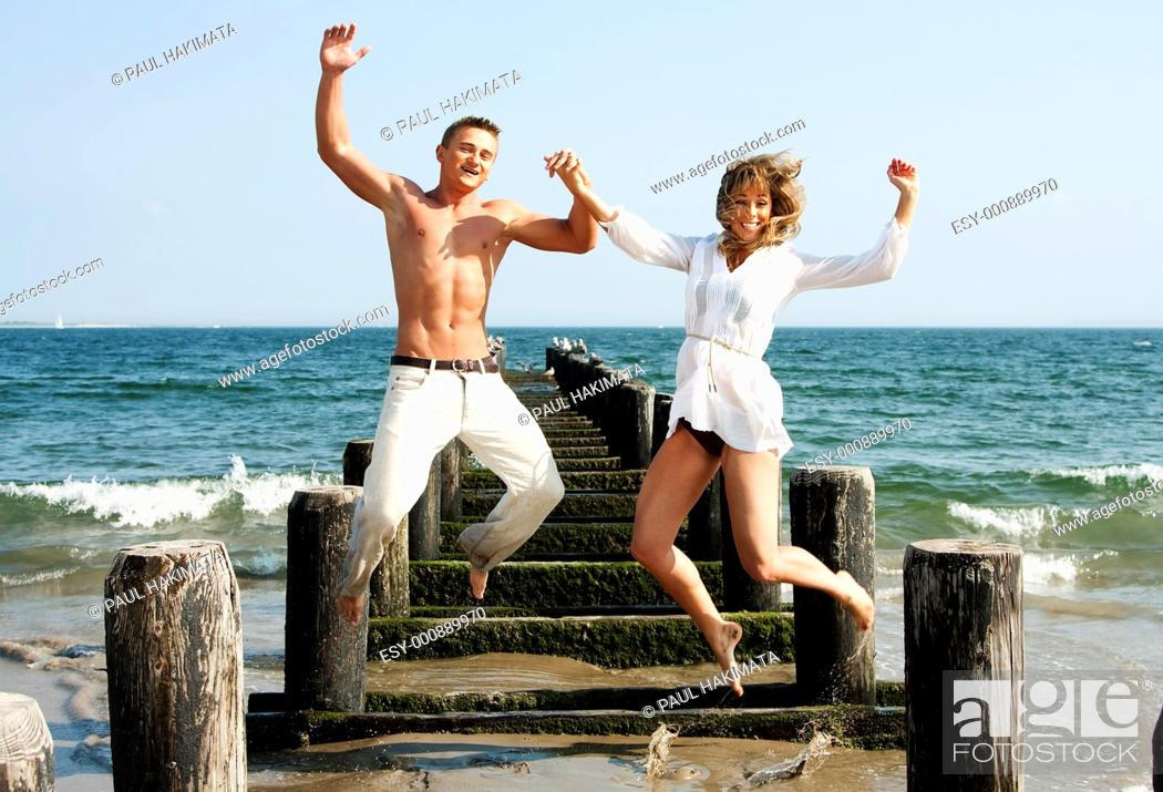 Stock Photo: Cute happy couple smiling jumping playfully at the beach with a pier and the ocean water in the background heaving fun.