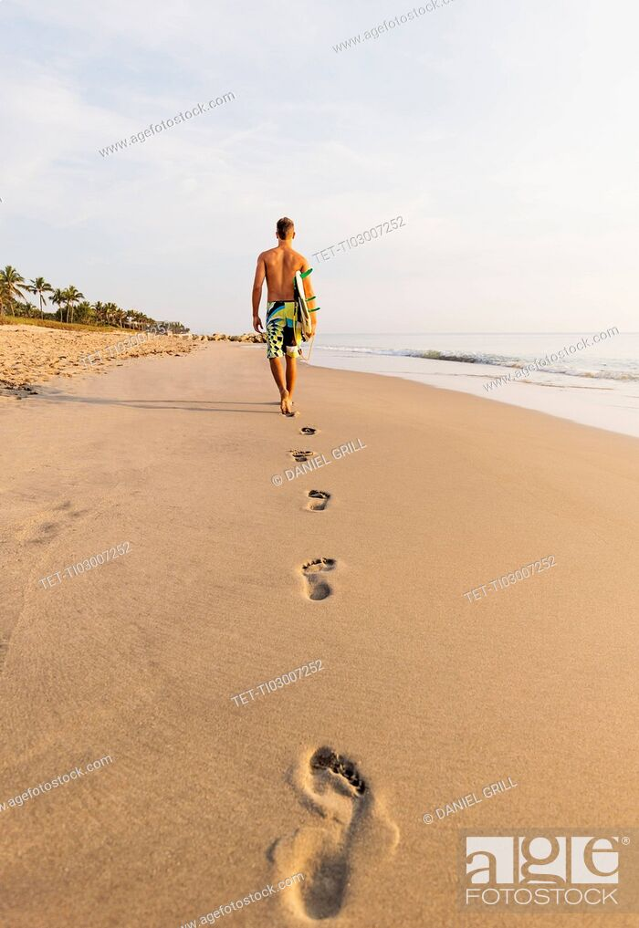 Stock Photo: Rear view of surfer on beach.