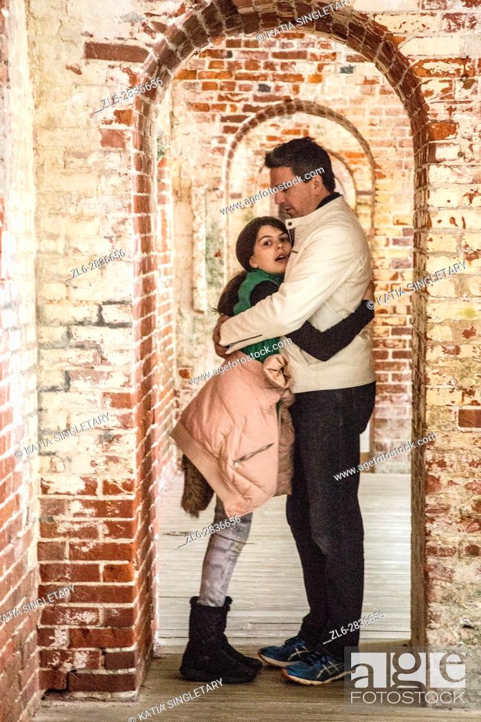 Stock Photo: Handsome dark hair father with a white leather jacket with his preteen daughter in the between of the arched doors of an old Fort. He is hugging her.