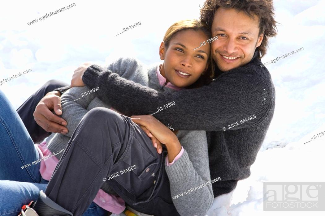 Stock Photo: Portrait of mixed race couple hugging in snow.