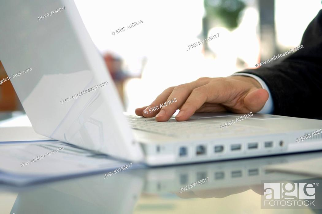 Stock Photo: Close-up of a businessman's hand using a laptop.