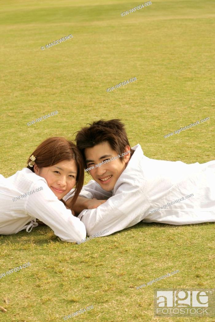 Stock Photo: A couple lying in the garden faces the camera.