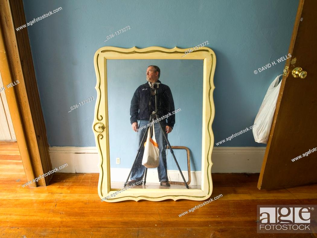 Stock Photo: Photographer photographs personal property left by former owners in a foreclosed house in Providence, Rhode Island, United States.