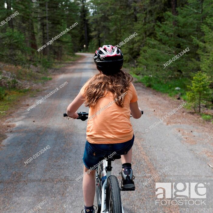 Stock Photo: Girl riding a bicycle, Jasper National Park, Alberta, Canada.