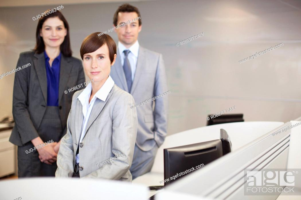 Stock Photo: Portrait of smiling business people at desk in office.