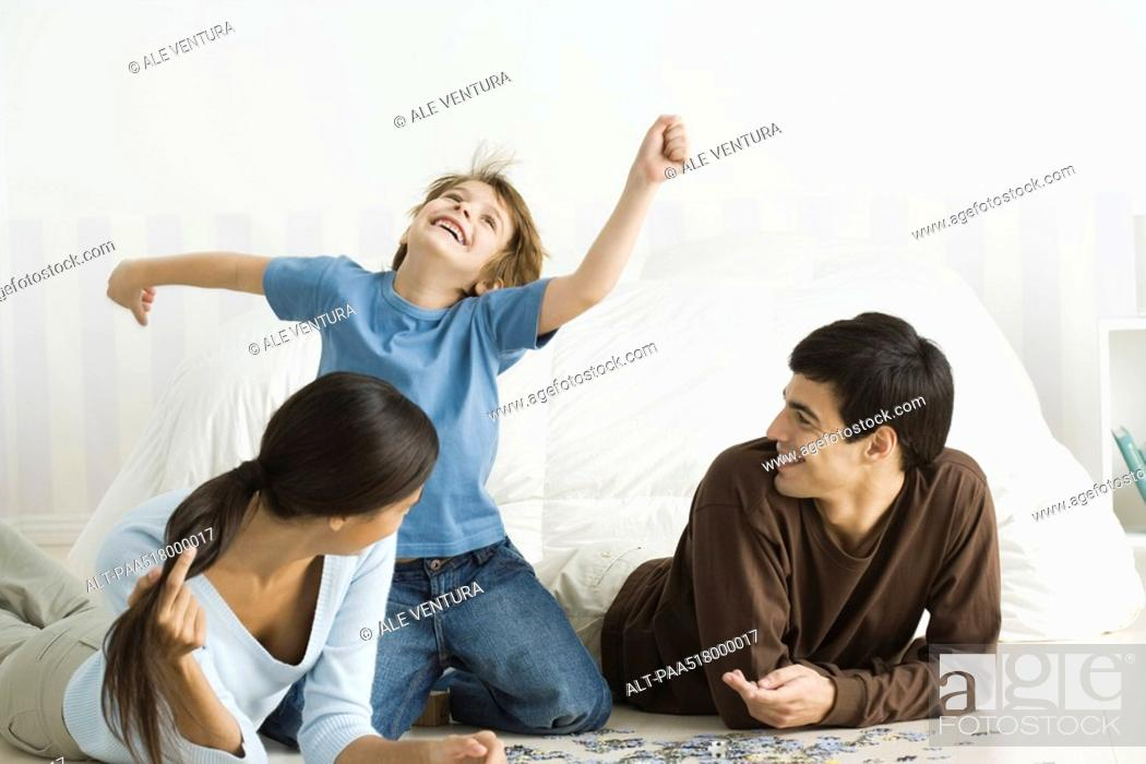 Stock Photo: Family playing with jigsaw puzzle in bedroom, boy laughing, arms raised.