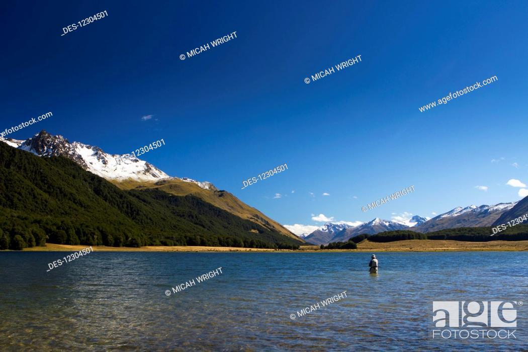 Stock Photo: A man practices fly fishing at Mavora Lake; Mavora, Southland, New Zealand.
