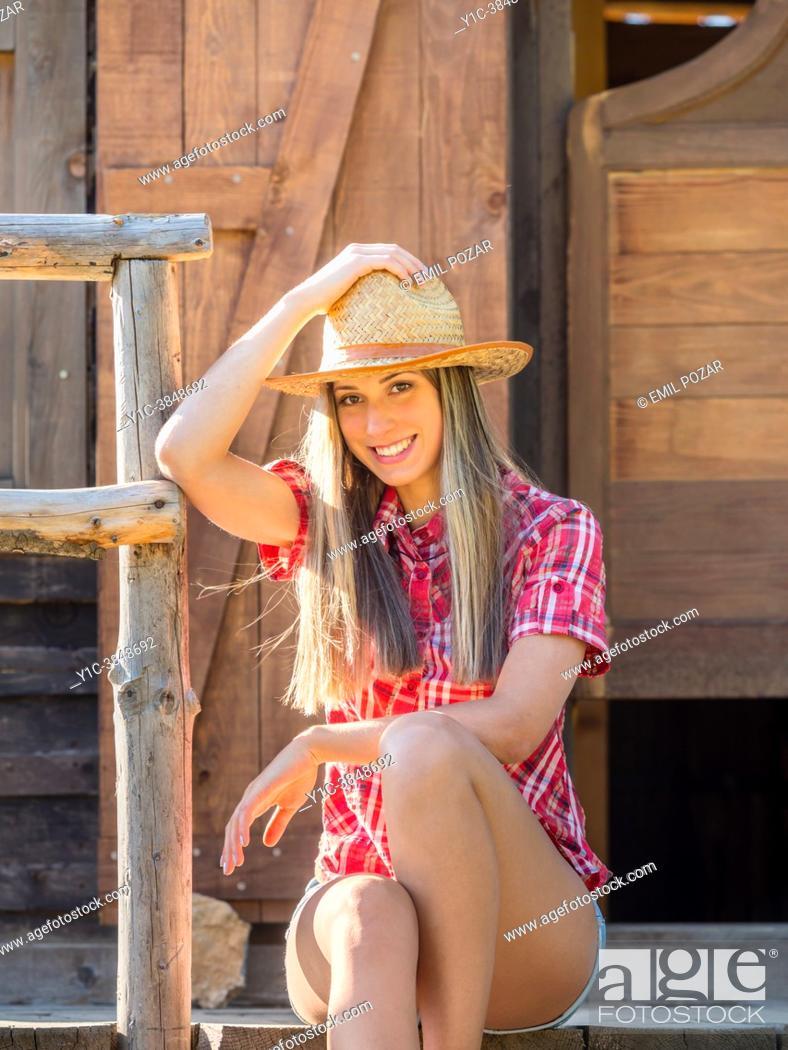 Stock Photo: Teen girl American West sitting on saloon entrance.
