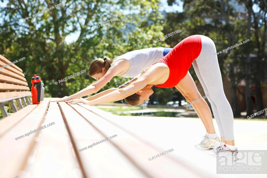 Stock Photo: Friends stretching on park bench.