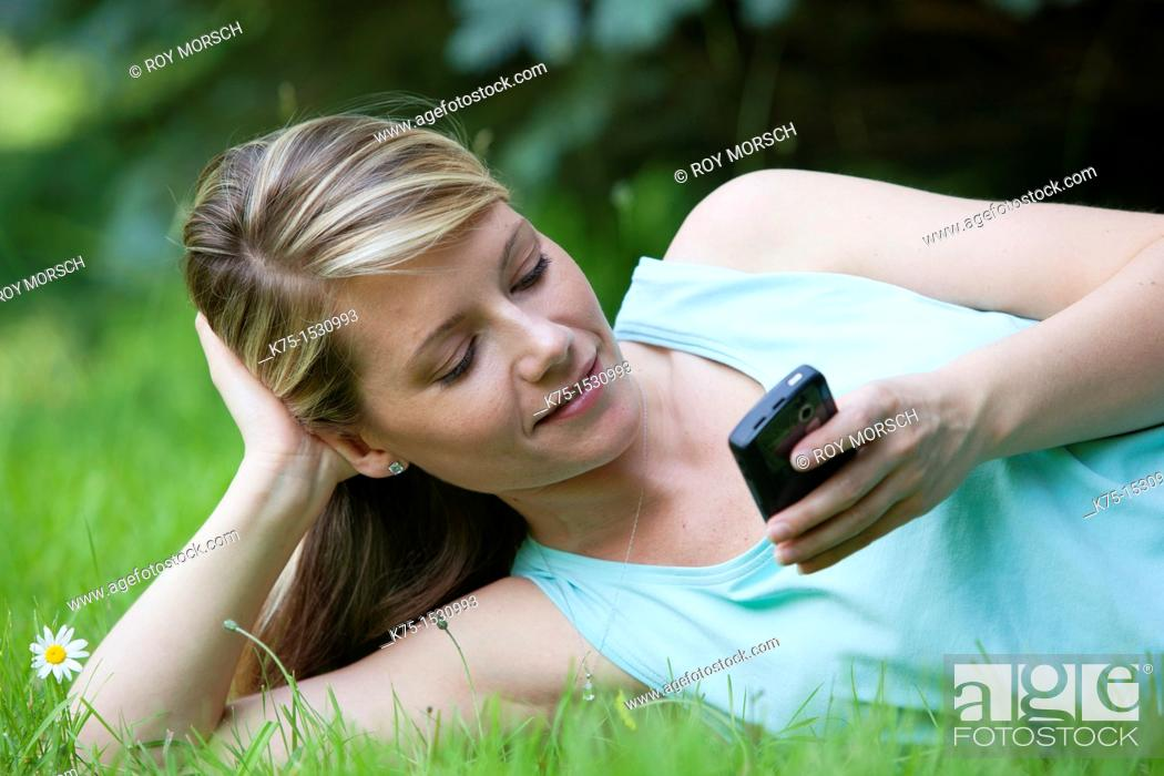 Stock Photo: Woman texting on her cell phone while relaxing on the lawn.