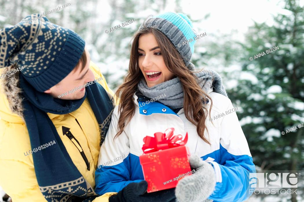 Stock Photo: Man giving red gift his girlfriend in winter time. Debica, Poland.