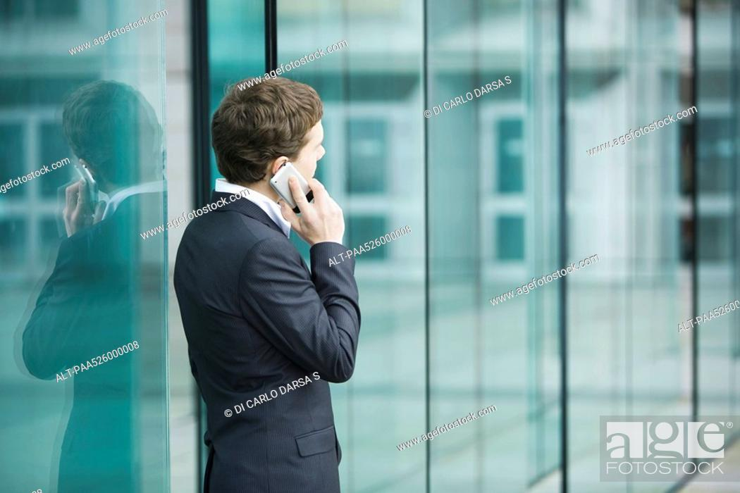 Stock Photo: Young businessman standing outside sliding glass doors talking on cell phone.