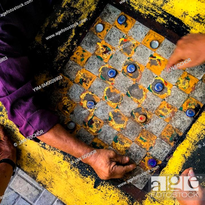 Stock Photo: Hands of Salvadoran men are seen moving crown caps while playing checkers on an outdoor checkerboard table in the park in San Salvador, El Salvador.