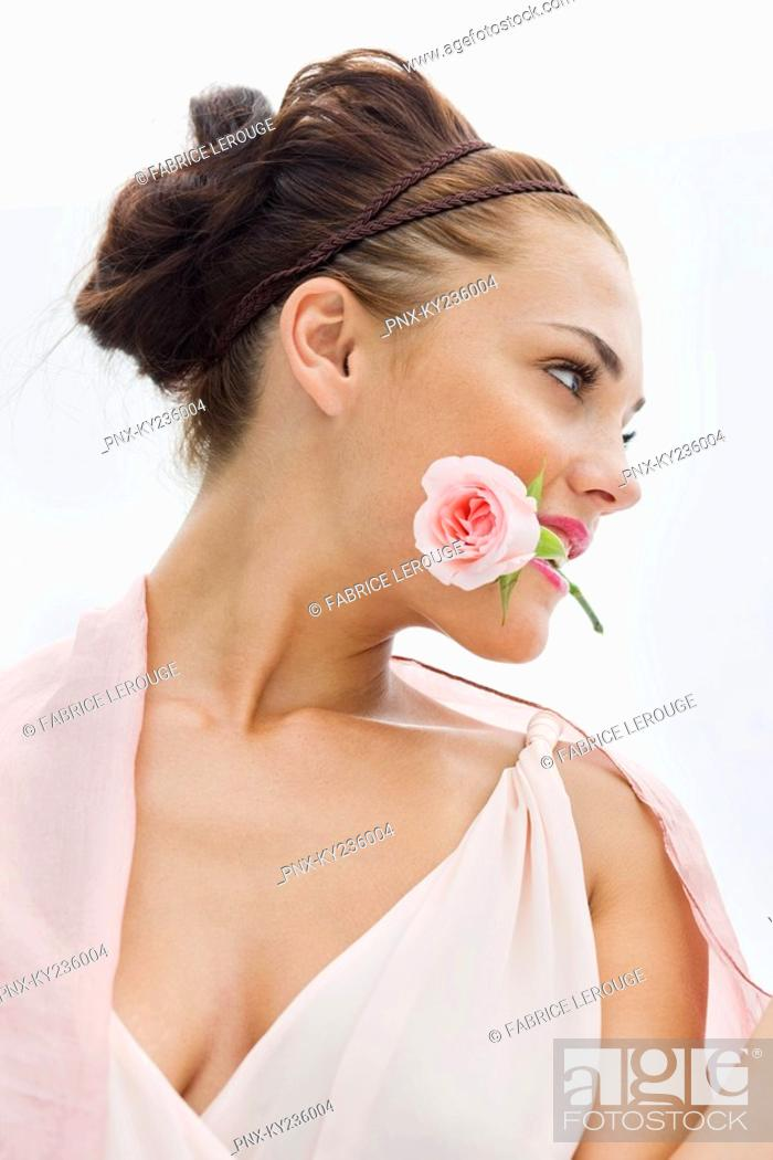Stock Photo: Fashion model holding rose between her teeth.