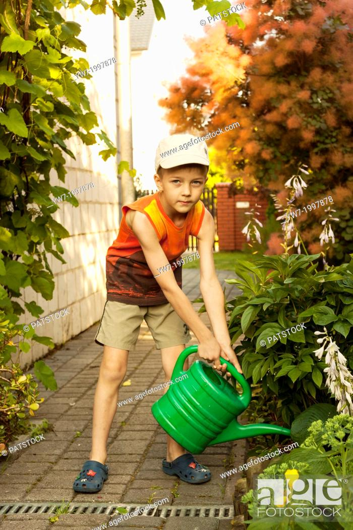 Stock Photo: Boy watering flowers with plastic green water can in a garden.