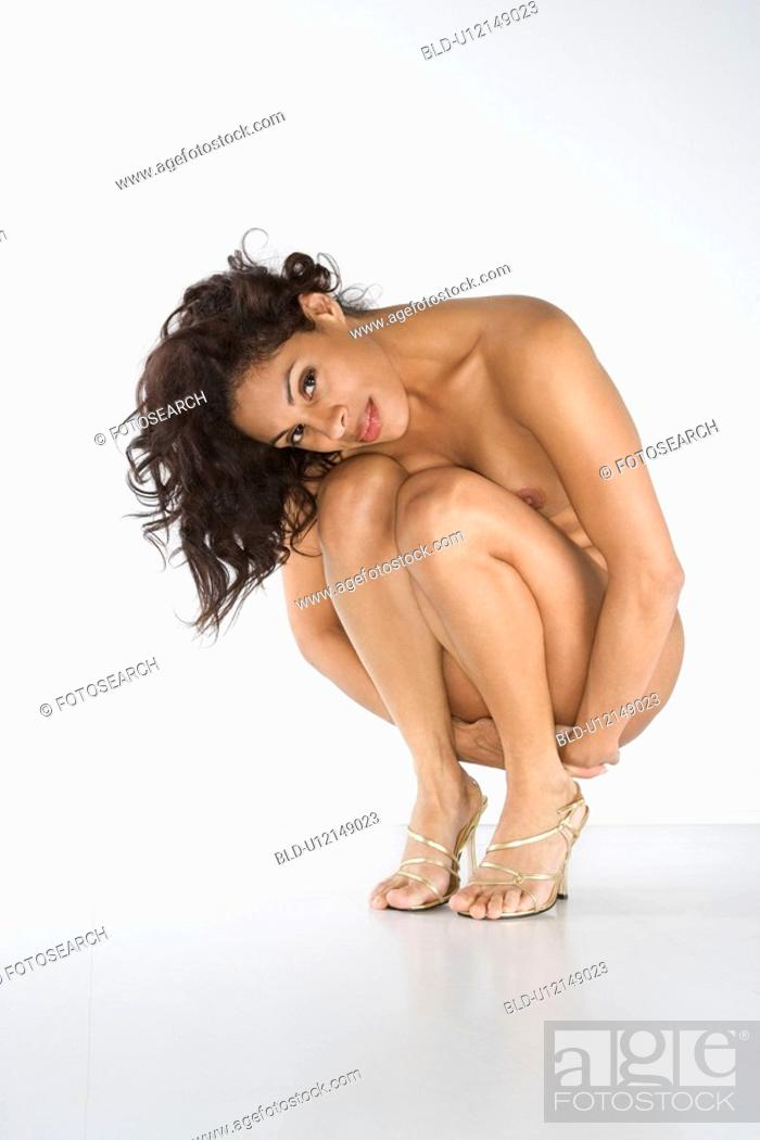 Stock Photo: Nude woman squatting on floor smiling.