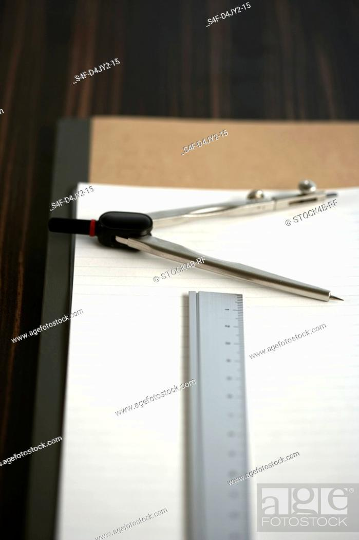 Stock Photo: Compasses and a ruler on a pad.