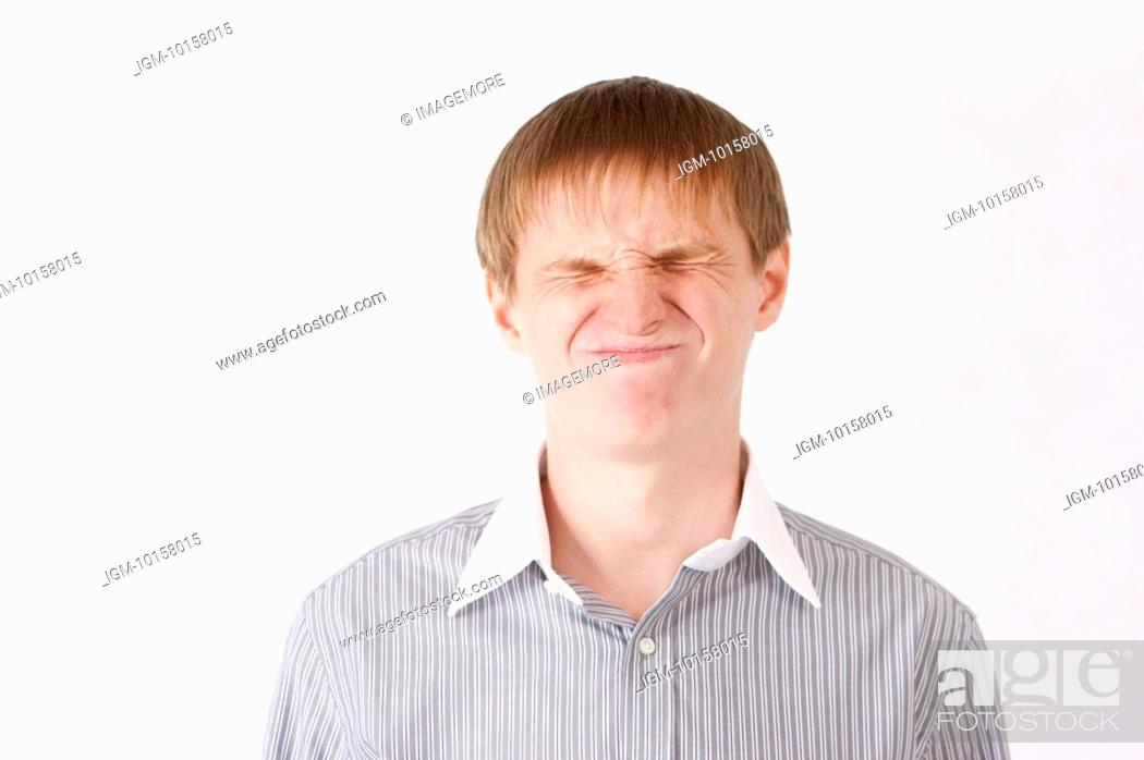 Stock Photo: Young man frowning with eyes closed.