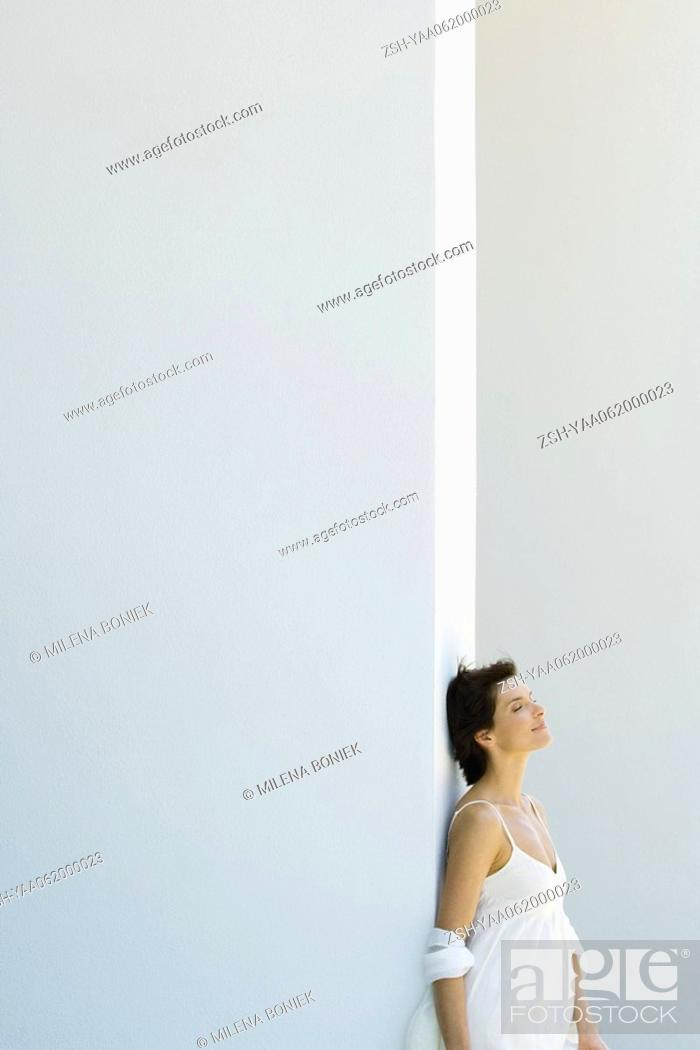 Stock Photo: Woman leaning against wall, head back, eyes closed, side view.