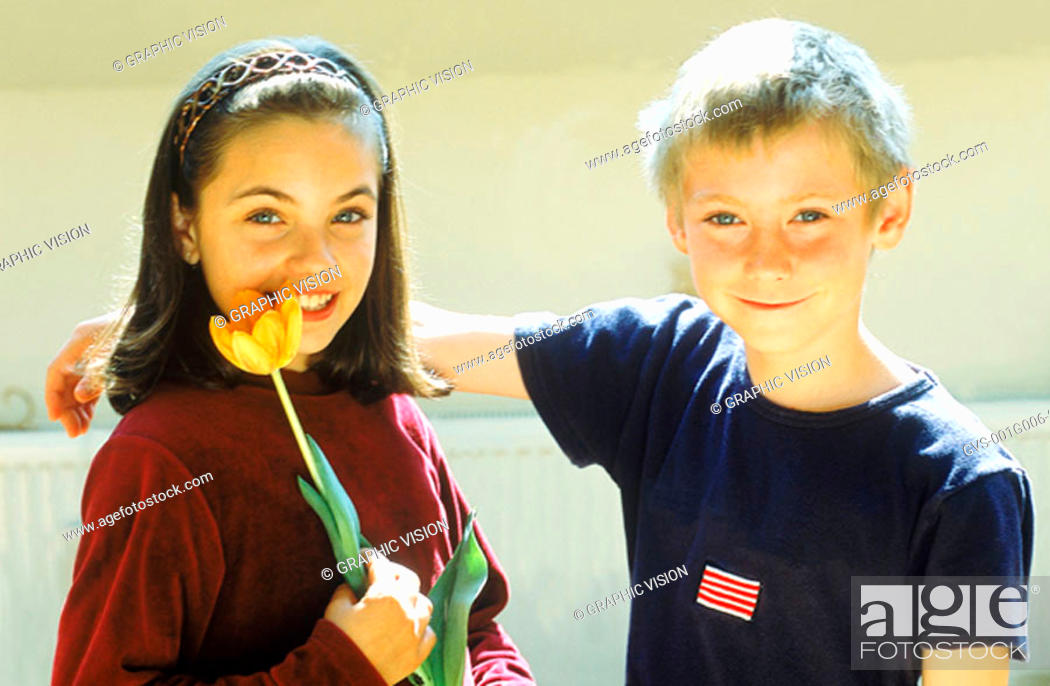 Stock Photo: Portrait of a young girl holding a flower and a young boy smiling.